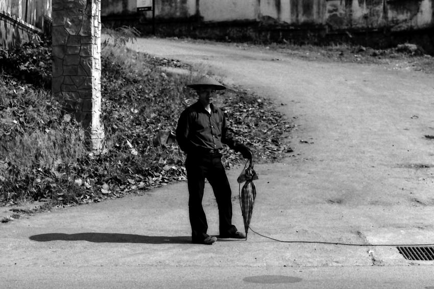 道路脇に立つ編笠を被った男