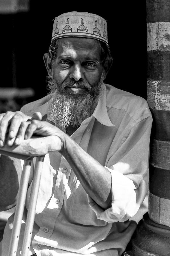 Man with a long beard resting in Jami Ul-Alfar Mosque
