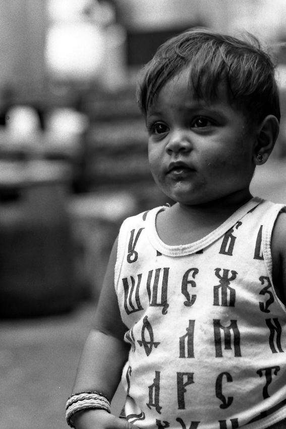 キリル文字がプリントされたシャツを着た男の子