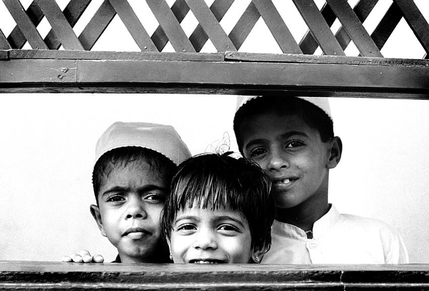 壁の向こう側に立つ三人の子ども