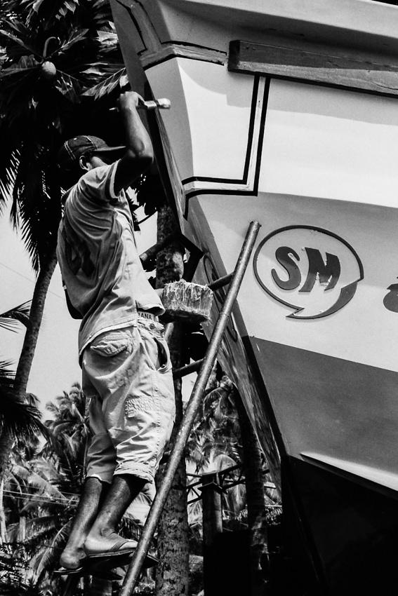 Man repainting fishing boat