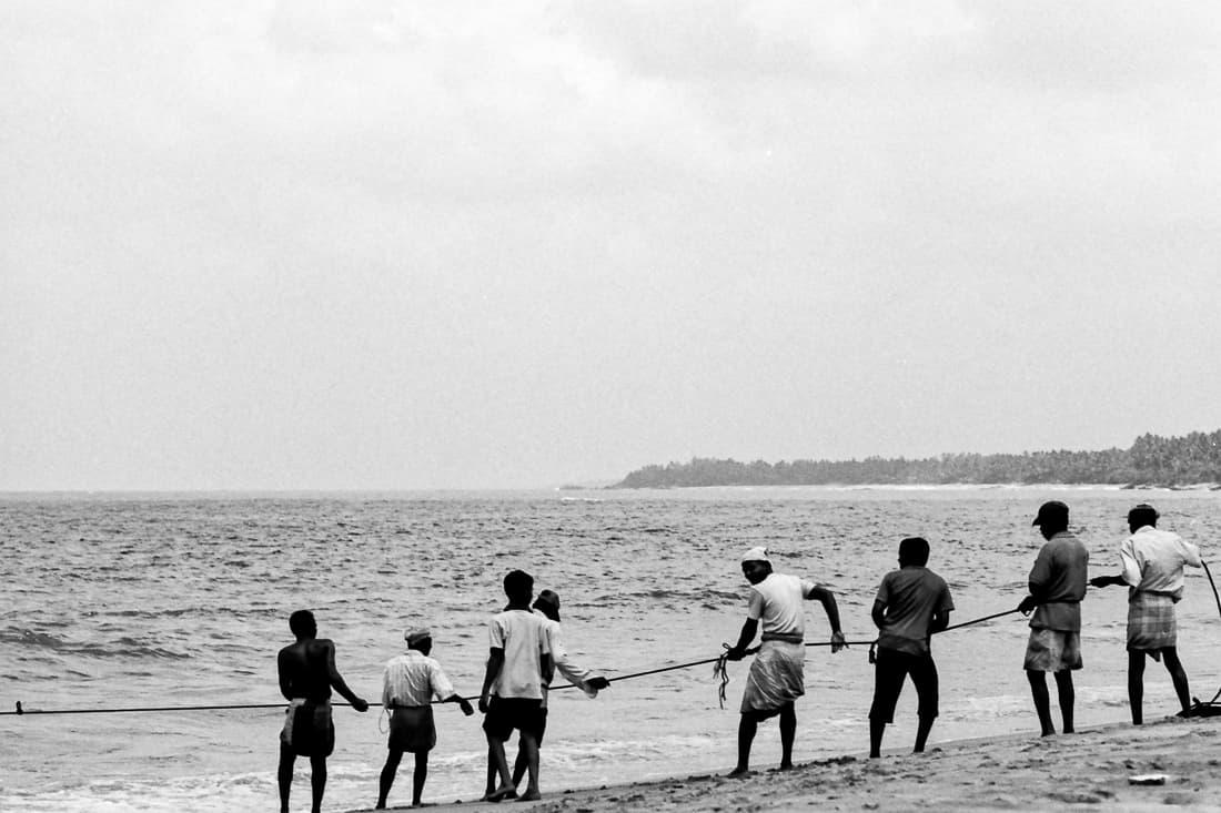 Fishermen dragging fishnet together