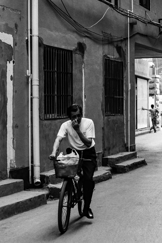 Man riding bicycle while scratching nose