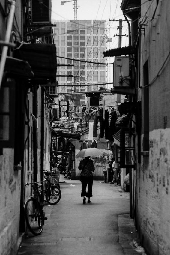 Woman walking putting umbrella up in lane