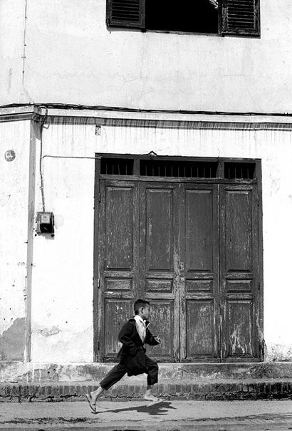 Boy Rushing Away In Front Of The Door @ Laos