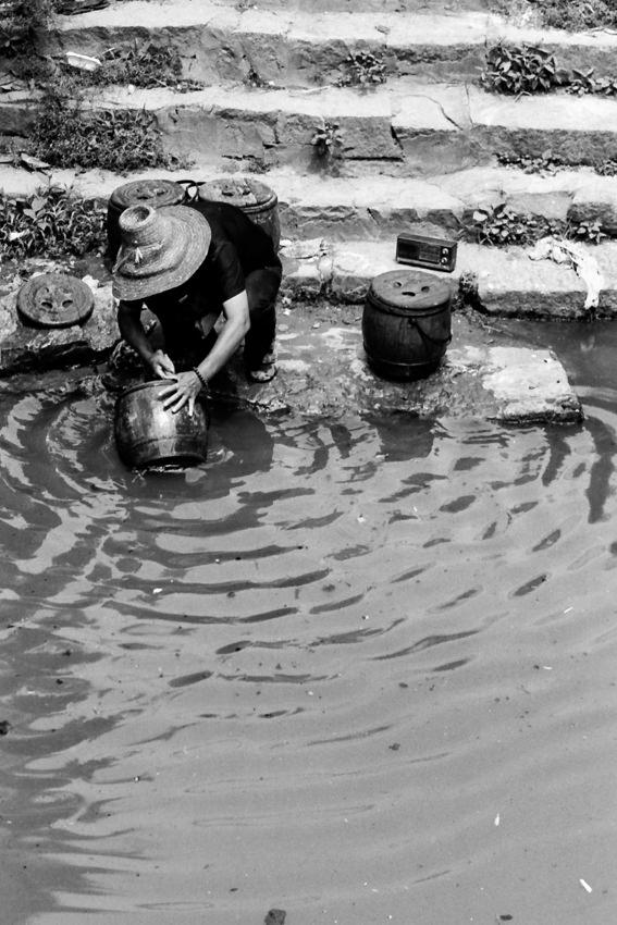 Woman washing jar with river water