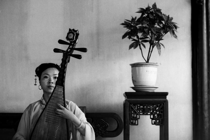 無表情で琵琶を奏でる女