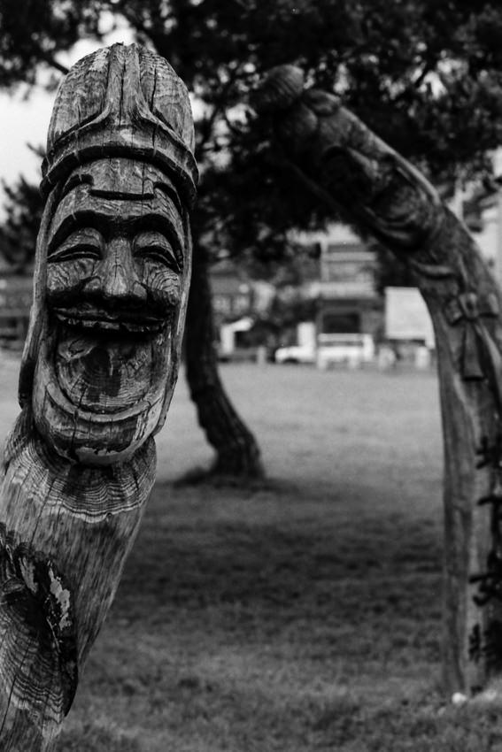 口を大きく開けて笑う木彫りの顔