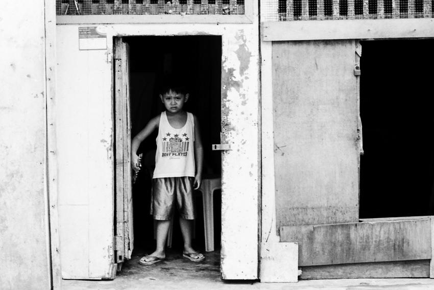 扉のところに立つ渋面の男の子