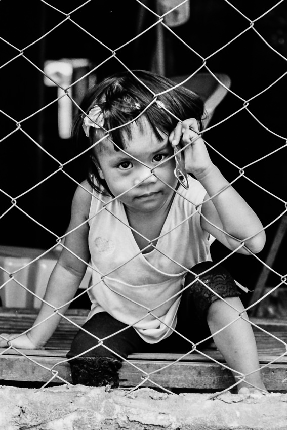 Girl sitting on the other side of wire netting
