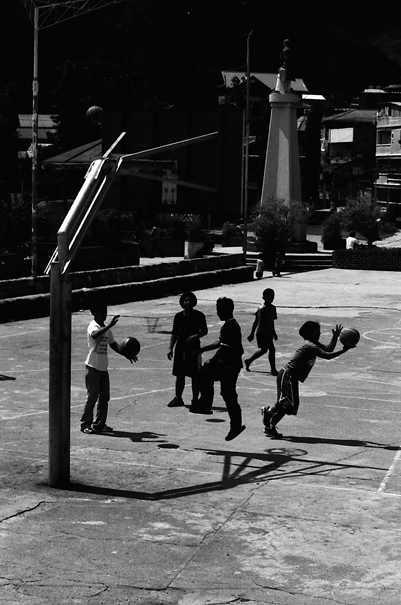 Silhouetted boys playing basketball