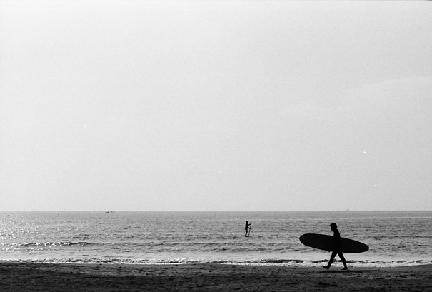 Silhouetted man carring surfborad