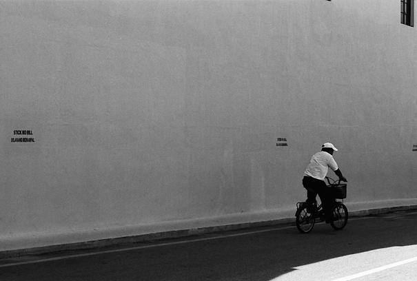 日陰の中を自転車で走る男