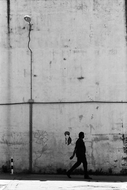 高い壁の前を歩く人影