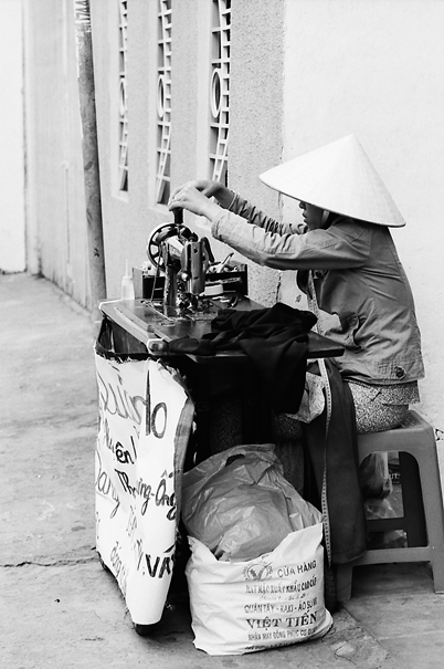 Woman working with sewing machine on sidewalk
