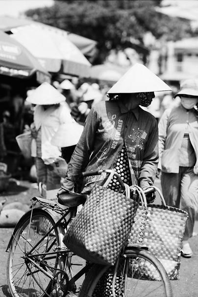 市場の中を自転車を押して歩いていた女