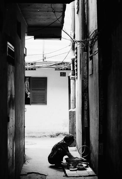 Figure doing housework in dim lane