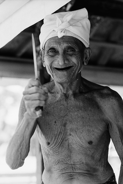 Smiling old man holding knife
