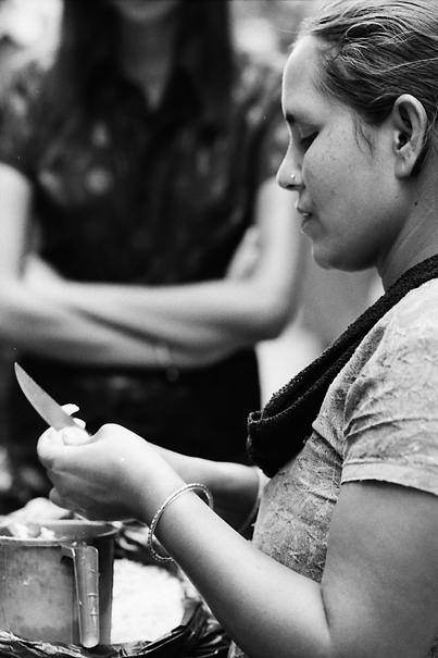 ナイフでマンゴーを切る女