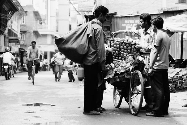 行商人からマンゴーを買う男