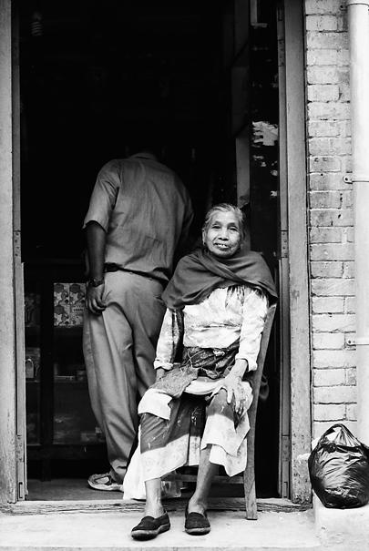 Older woman sitting in front of door