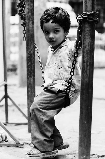 Boy sitting on chain alone