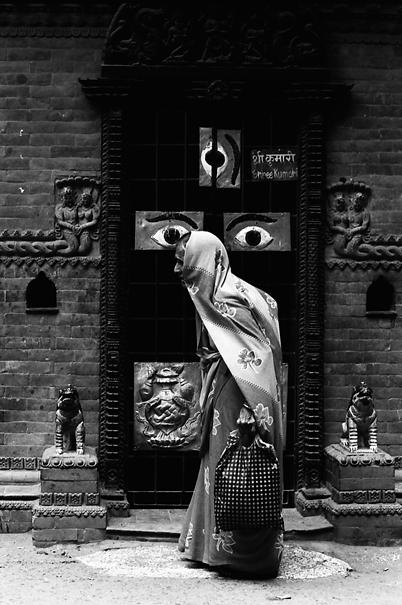 Older woman walking in front of door with eyes
