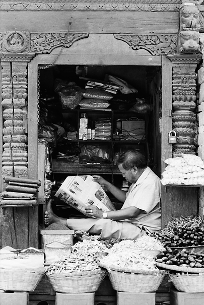 Storekeeper reading newspaper