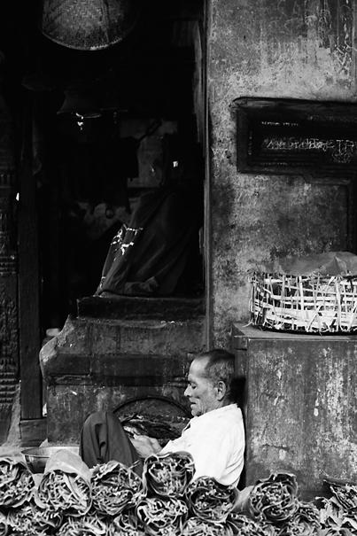 商品の横で休憩中の男