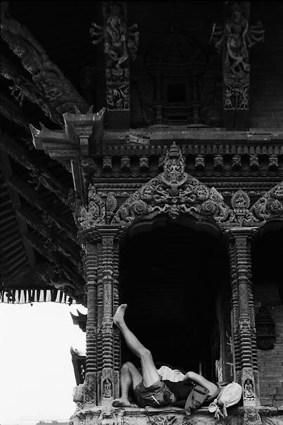 Man sleeping between decorative pillars