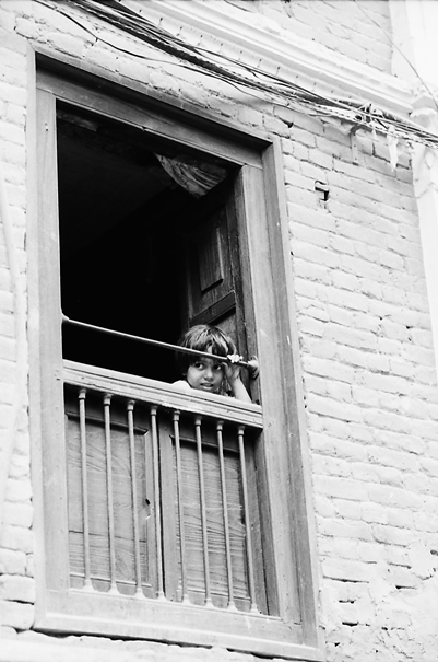 Girl peeking through upstairs window