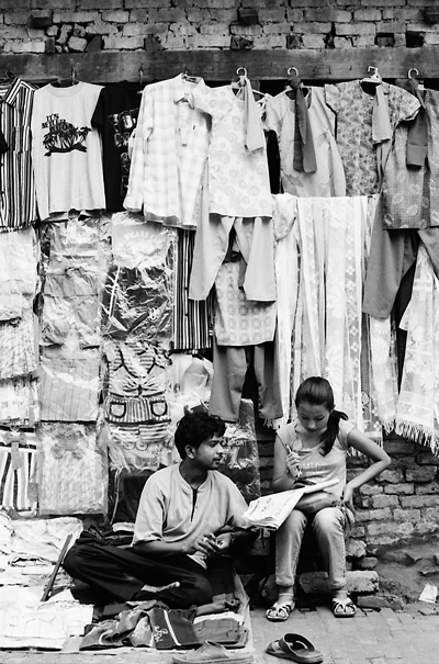 Man and woman selling clothes on street