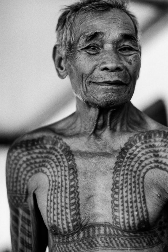 Old man showing tattooed chest