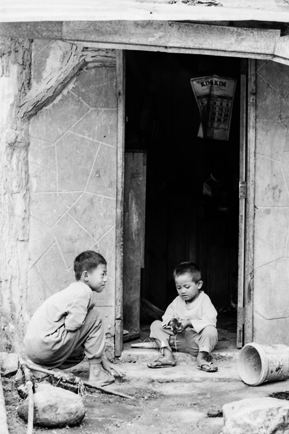 Two boys playing in front of house