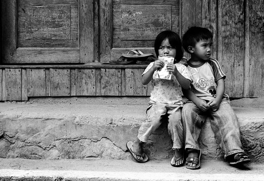道端で寄り添って座る男の子と女の子