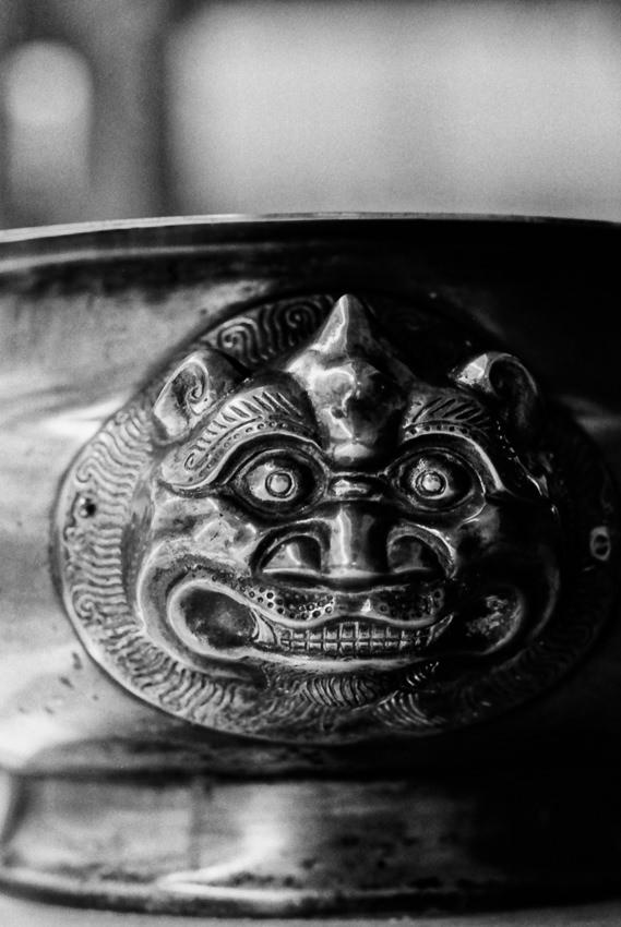 grotesque face sculptured on bowl