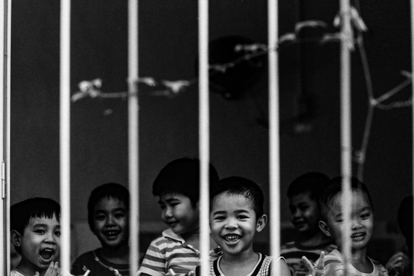 柵の向こう側で遊ぶ子どもたち