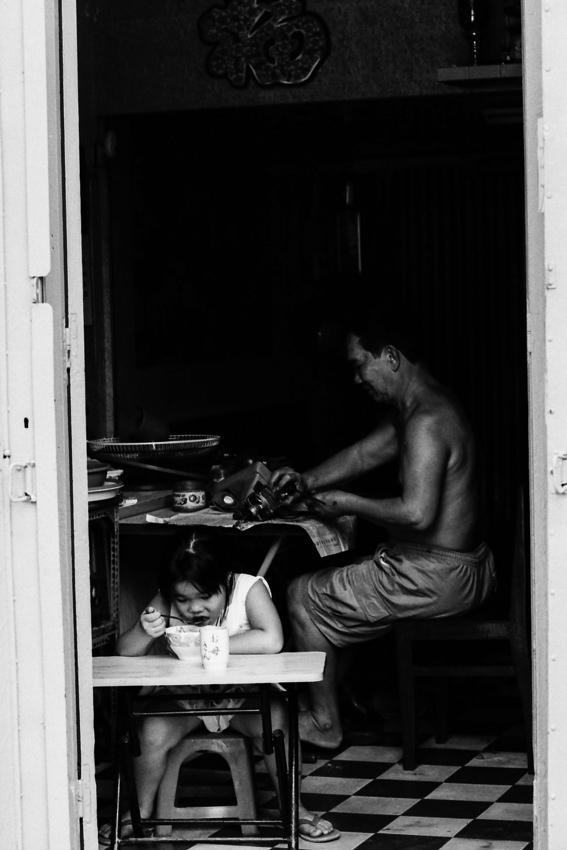 ご飯を食べる女の子と働くお父さん