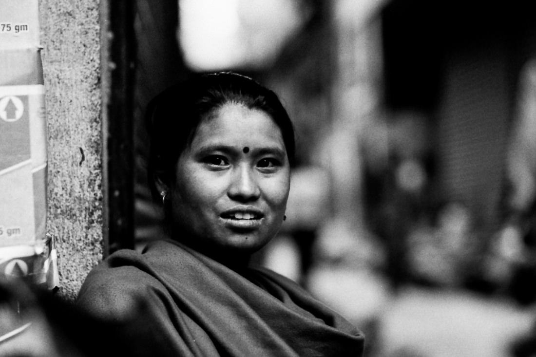 Woman sitting in corner of street