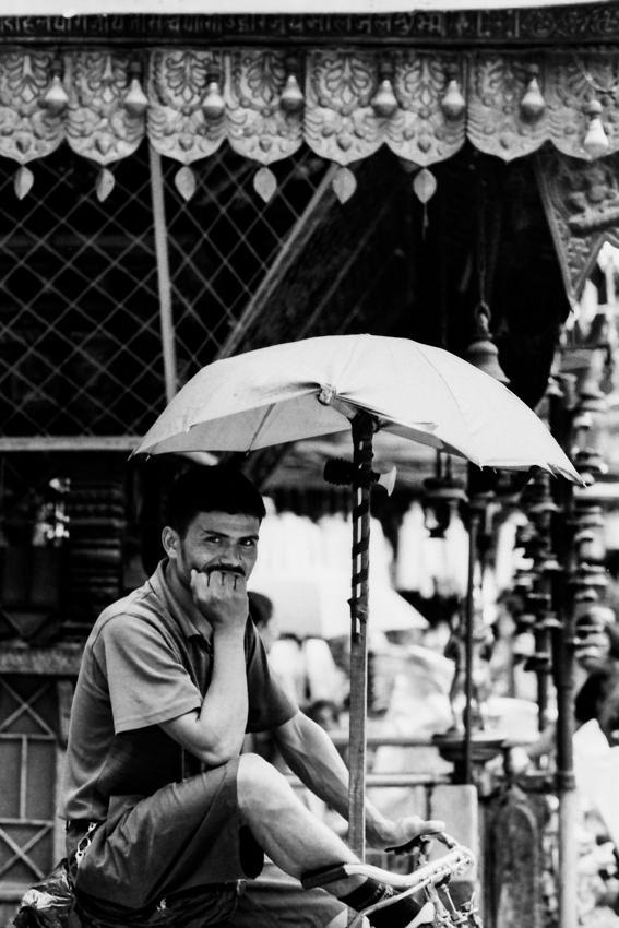 Man waiting for customer under umbrella