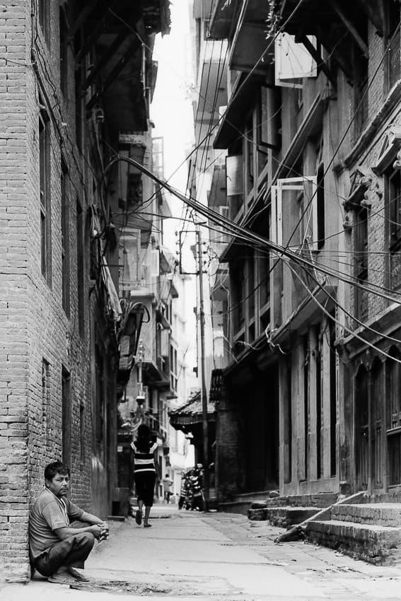 Man crouching in street corner