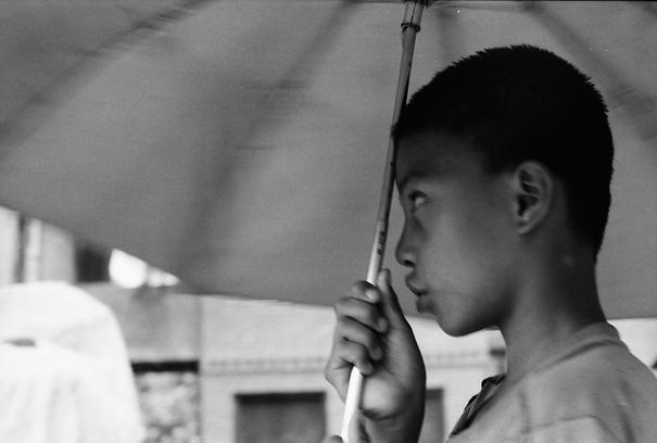 Boy gripping umbrella handle tightly