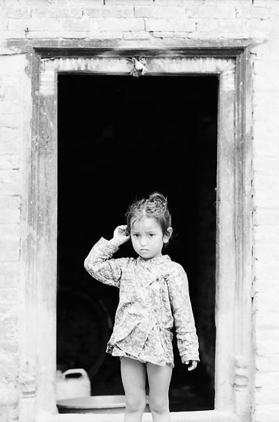 Little girl standing in front of door