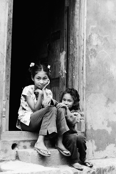 Sister sitting together in front of door