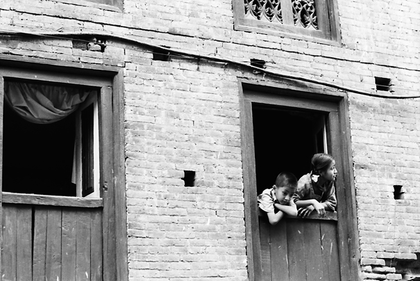 Boy and girl leaning out of window