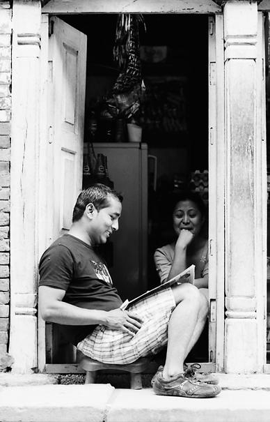 玄関先で新聞を読む男