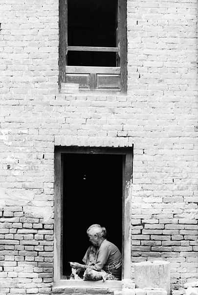 Older Woman Working At The Door @ Nepal