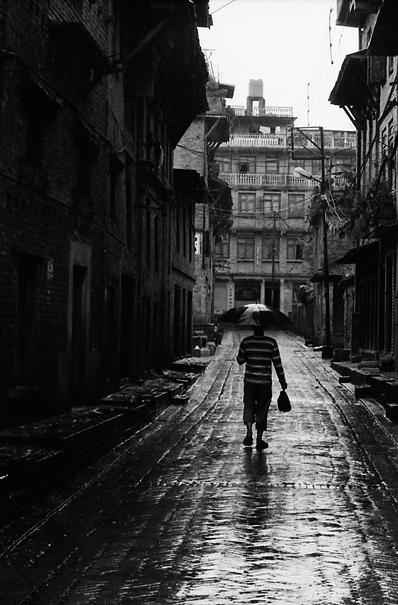 Man walking putting umbrella up
