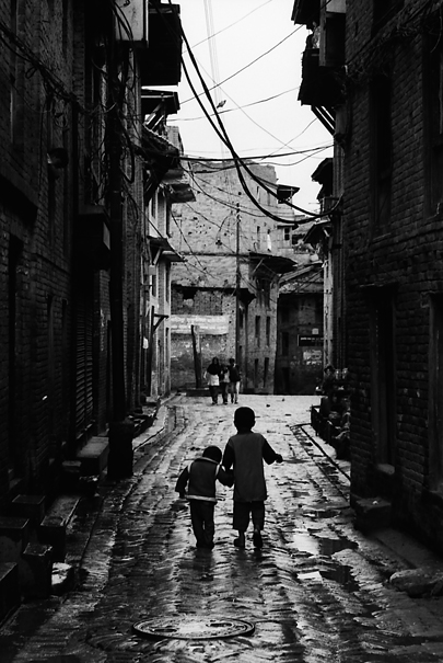 Little brothers walking together in dim lane