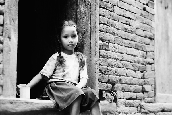 Girl sitting at entrance of house
